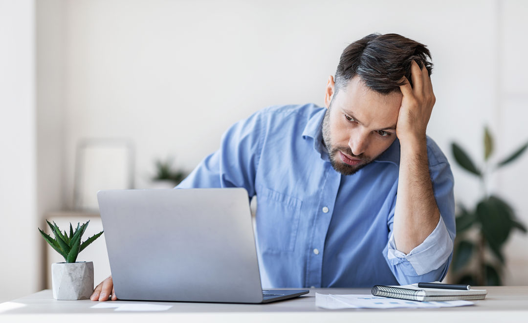 Stressed man at a desk with hand on forehead, maybe due to insolvency or other business issues